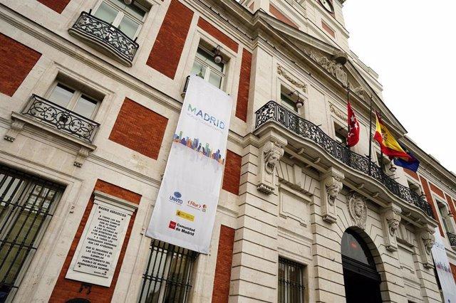 Archivo - Imagen de la Real Casa de Correos, sede del Gobierno regional, con una lona para promocionar la Feria Internacional de Turismo (FITUR).