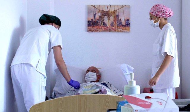 Dos trabajadoras de una residencia de mayores atienden a un usuario