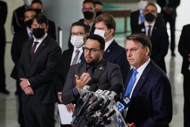 HANDOUT - 31 March 2021, Brazil, Brasilia: Brazilian president Jair Bolsonaro (R) speaks during a press conference at the Planalto Palace. Photo: Isac Nobrega/Palacio Planalto/dpa - ATTENTION: editorial use only and only if the credit mentioned above is r