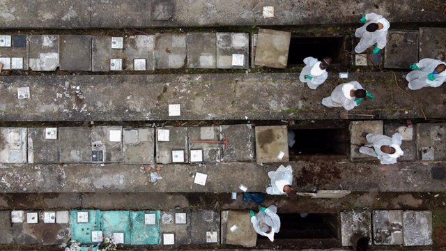 Los empleados del cementerio de Nova Cachoeirinha, el segundo más grande de Sao Paulo (Brasil), retiran los huesos de las tumbas antiguas para hacer sitio a los nuevos muertos por la COVID-19.