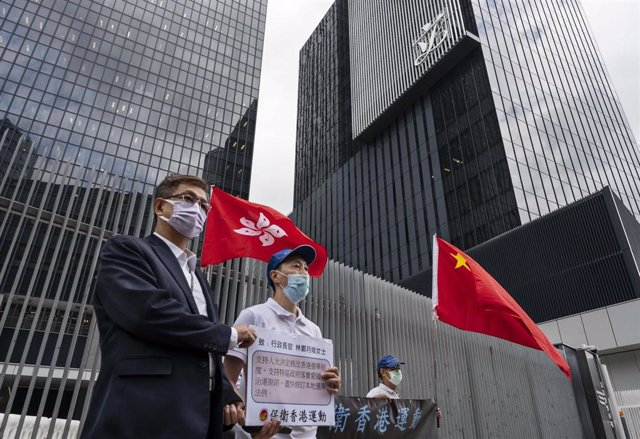 31 March 2021, China, Hong Kong: Pro-Hong Kong Government supporters hold China and Hong Kong flags as they gather outside the Hong Kong government headquarters building to show their support to the government's policy of reforming the electoral system by