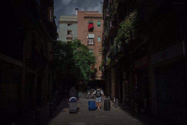 Archivo - Un turista camina amb maletes a Barcelona. (Arxiu)