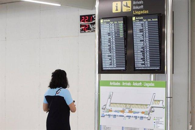 Una pasajera observa la pantalla del aeropuerto de Palma.