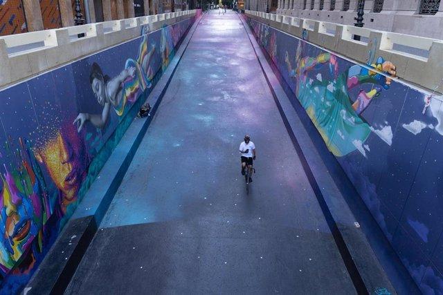 Un ciclista circula por una calle vacía.
