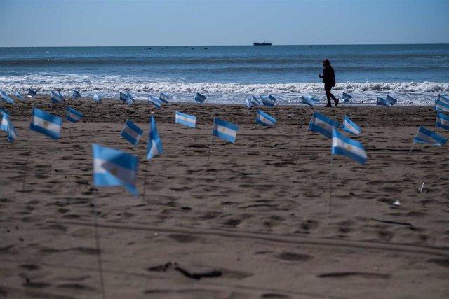 Archivo - Banderas de Argentina en una playa en conmemoración a las víctimas de la pandemia.