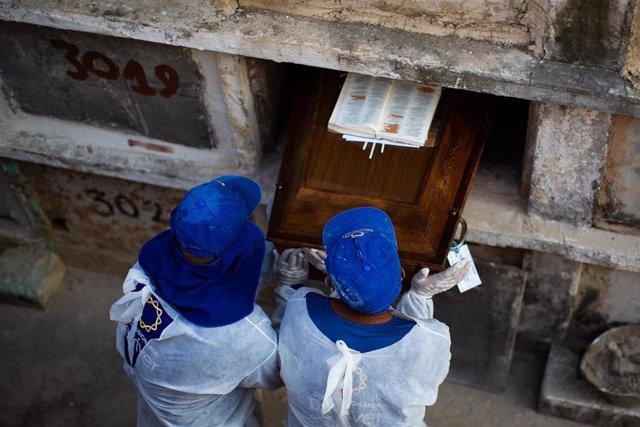 Los trabajadores del cementerio entierran a una  víctima del coronavirus en el cementerio de Caju el 24 de marzo de 2021 en Río de Janeiro, Brasil.