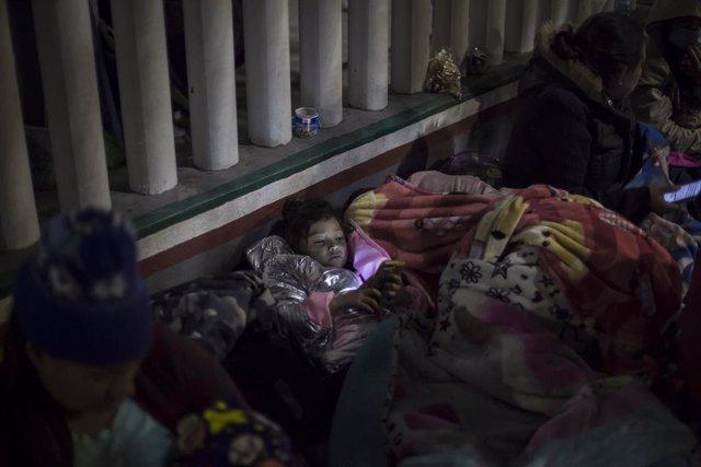 Archivo - Una niña mira un celular mientras duerme en la explanada del Instituto Nacional de Migración cerca del paso fronterizo El Chaparral, entre migrantes centroamericanos y mexicanos.