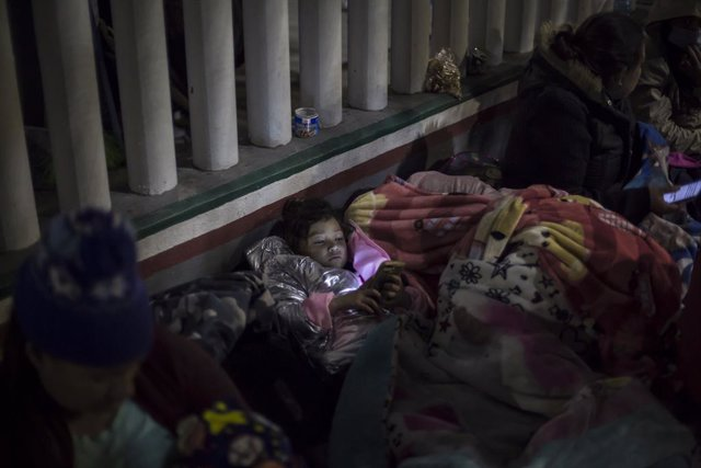 Archivo - 19 February 2021, Mexico, Tijuana: A girl looks at a cell phone while sleeping on the esplanade of the National Institute of Migration near the El Chaparral border crossing, among Central American and Mexican migrants waiting for US authorities