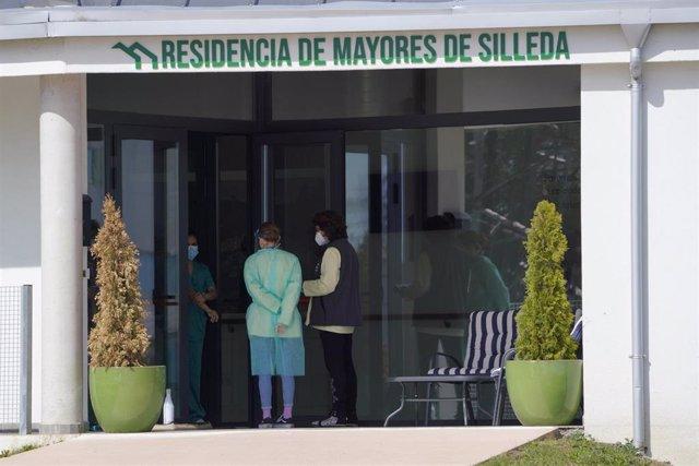 Dos mujeres, frente a la entrada de la residencia de mayores Coviastec, en Silleda, Pontevedra, Galicia (España), a 22 de marzo de 2021. El brote de coronavirus vinculado a este geriátrico alcanzó ayer los 46 usuarios infectados tras detectarse 13 nuevos