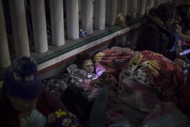 Archivo - Arxivo - Una nena mira un cel·lular mentre dorm a l'esplanada de l'Institut Nacional de Migració prop del pas fronterer El Garriga, entre migrants centroamericanos i mexicans.