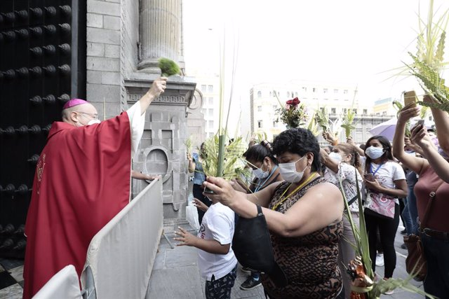 28 March 2021, Peru, Lima: A priest blesses worshippers outside the Basilica of St. Francis in Lima. Photo: El Comercio/GDA via ZUMA Wire/dpa