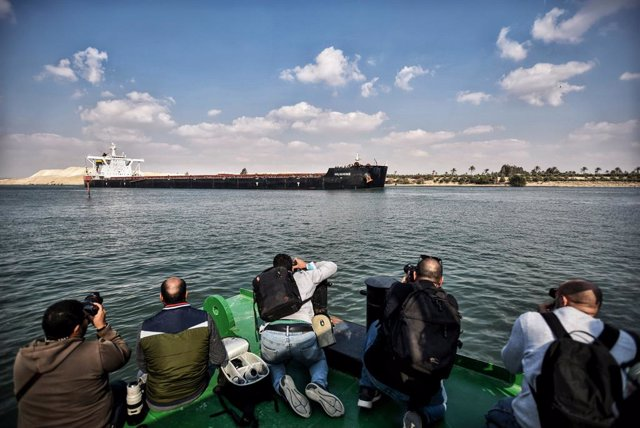 """30 March 2021, Egypt, Ismailia: Photographers take pictures of ships sailing through the Suez Canal as traffic resumes after the """"Ever Given"""" container ship operated by the Evergreen Marine Corporation, was freed after blocking the waterway route for almo"""