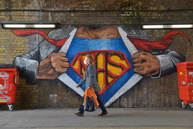 01 April 2021, United Kingdom, London: A woman walks past a graffiti tribute to National Health Service in Waterloo, amid the coronavirus (COVID-19) pandemic. Photo: Thomas Krych/SOPA Images via ZUMA Wire/dpa