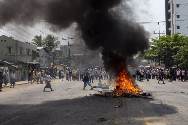 31 March 2021, Myanmar, Yangon: Protesters stand behind burning tires during a demonstration against the military coup and the detention of civilian leaders. Photo: Thuya Zaw/ZUMA Wire/dpa