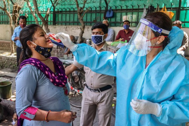 02 April 2021, India, New Delhi: A health worker collects swab sample from a woman for Coronavirus (Covid-19) PCR test at the road side in New Delhi. Photo: Naveen Sharma/SOPA Images via ZUMA Wire/dpa
