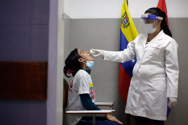 """25 March 2021, Venezuela, Caracas: A doctor from the CDI health center administers a dose of Carvativir, popularly known as the """"miracle droplet against Corona"""", to a health worker. Photo: Jesus Vargas/dpa"""
