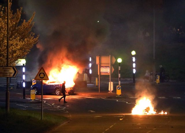 03 April 2021, United Kingdom, Belfast: A man walks past a burning car after violence broke out in Newtownabbey. Photo: Peter Morrison/PA Wire/dpa