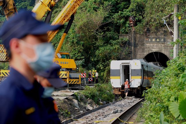 03 April 2021, Taiwan, Hualien: A damaged train carriage is lifted and removed from a track for clearance after a train collided with a truck and derailed in eastern Taiwan the day before. Flags were at half-mast in Taiwan on Saturday and were set to stay