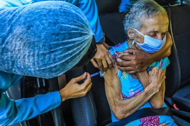 01 April 2021, Brazil, Rio De Janeiro: An elderly woman receives the Butantan vaccine at the Museu da Replica, in the Catete neighborhood, during a vaccination campaign against the Coronavirus (Covid-19). Photo: Ellan Lustosa/ZUMA Wire/dpa