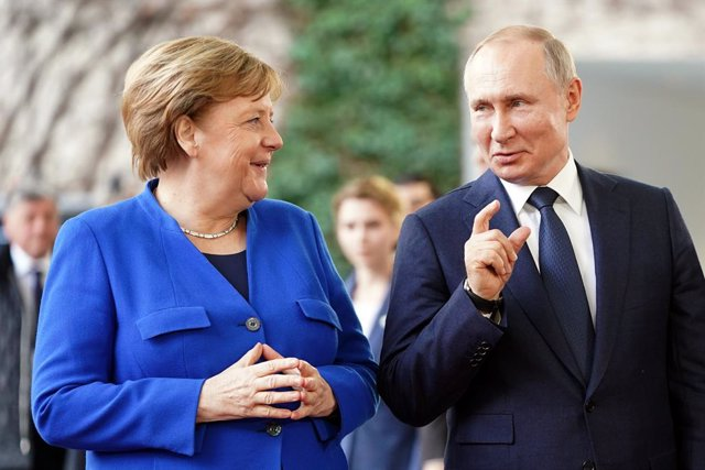 Archivo - FILED - 19 January 2020, Berlin: German Chancellor Angela Merkel (L) receives Russian President Vladimir Putin, at the Federal Chancellery before the International conference on Libya. Putin held a phone conversation with Merkel about closer coo