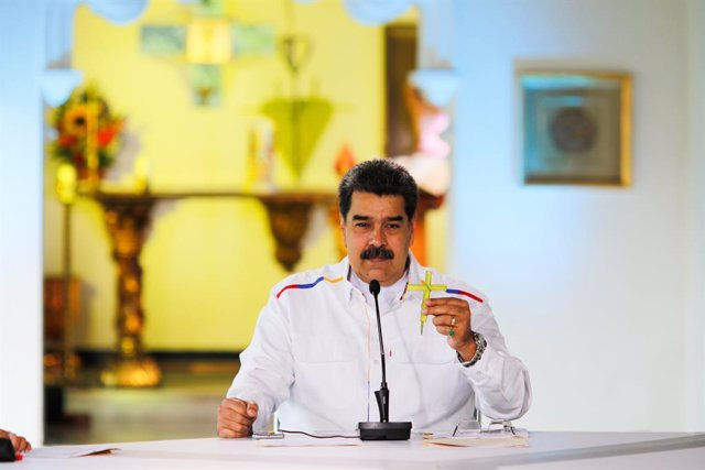 HANDOUT - 28 March 2021, Venezuela, Caracas: Nicolas Maduro, president of Venezuela, holds a cross during a press conference. Maduro has offered to swap oil for COVID-19 vaccines in view of rapidly rising coronavirus numbers as well as US sanctions agains
