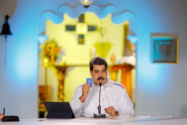 HANDOUT - 28 March 2021, Venezuela, Caracas: Nicolas Maduro, president of Venezuela, holds a copy of the Venezuelan constitution during a press conference. Maduro has offered to swap oil for COVID-19 vaccines in view of rapidly rising coronavirus numbers