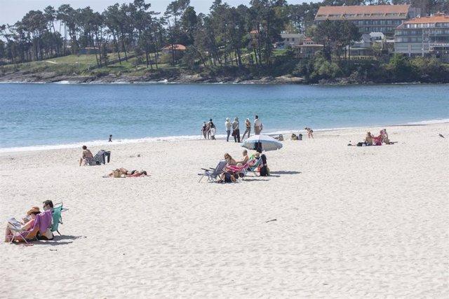 Varias personas en la playa de Sanxenxo, en Pontevedra, Galicia (España), a 27 de marzo de 2021. El subcomité clínico mantiene el nivel alto de restricciones en el concello de Sanxenxo, lo que conlleva que la hostelería solo puede servir en las terrazas y