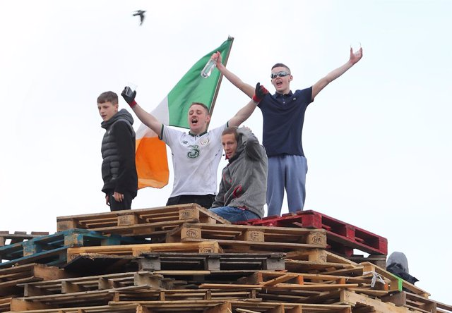 Archivo - 08 August 2019, Northern Ireland, Belfast: People stand at the site of a proposed bonfire in north Belfast, which contractors have been ordered to remove. A stand-off has developed between police and those supporting the bonfire, and a number of