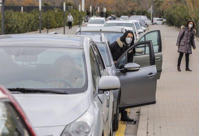 Archivo - Una mujer sale de su vehículo mientras espera para realizarse una prueba PCR