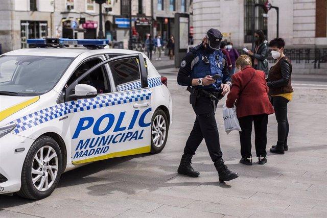 Un agente de Policía Municipal de Madrid y un vehículo de la misma, en la Puerta del Sol, en Madrid (España).