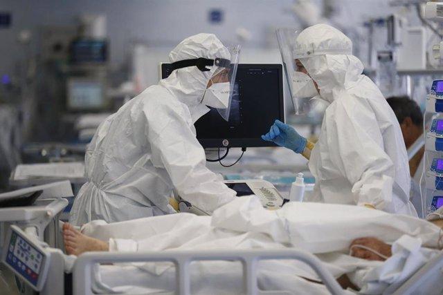 Profesionales sanitarios atienden a un enfermo de COVID-19 en la capital italiana, Roma.