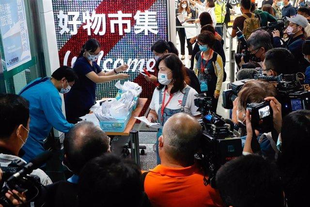 Trabajadores de la salud recolectan pruebas de coronavirus de los viajeros en el aeropuerto de Taoyuan.