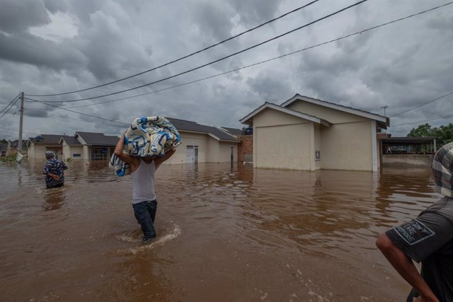 29 March 2021, Indonesia, Pekanbaru: Residents salvage belongings after floodwaters submerged their homes following heavy rains. Photo: Afrianto Silalahi/ZUMA Wire/dpa
