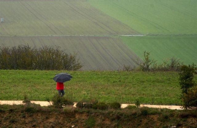 Archivo - Una persona se refugia con un paraguas de la lluvia en Vitoria, País Vasco (España), a 19 de marzo de 2021.