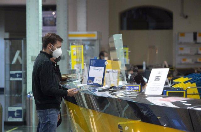 Un cliente es atendiendo en la Oficina de Correos de Cibeles, en Madrid, (España).