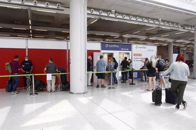 Pasajeros hacen cola para entrar al dispositivo de detección de Covid-19 colocado en el aeropuerto de Palma de Mallorca.