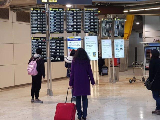 Archivo - Pasajeros en paneles del aeropuerto de Madrid- Barajas (España).