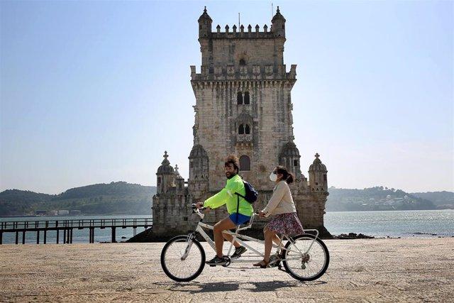 Personas en bicicleta ante la Torre de Belem en Lisboa