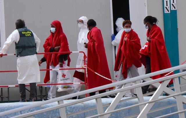 Varias personas se bajan de un barco tras ser rescatadas de una patera al sur de Fuerventura, a 6 de abril de 2021.