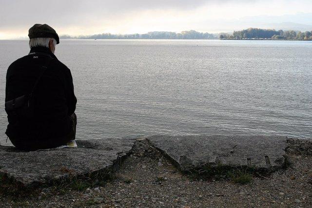 Archivo - Un hombre sentado frente a un lago.