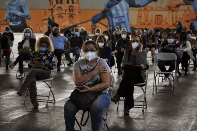 Fila de pacientes que esperan sentados tras recibir la primera dosis de la vacuna AstraZeneca en el recinto de Expourense, a 6 de abril de 2021, en Ourense, Galicia (España).
