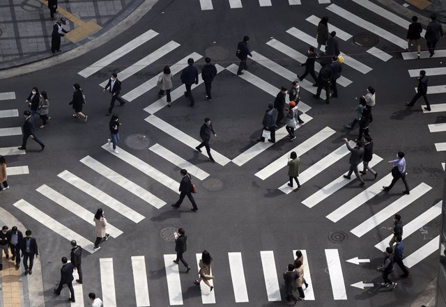 26 March 2021, South Korea, Seoul: Pedestrians cross a zebra intersection in Seoul. The South Korean government decided on Friday to extend ongoing second-level social distancing rules that were originally set to expire on 28 March 2021, including a ban o