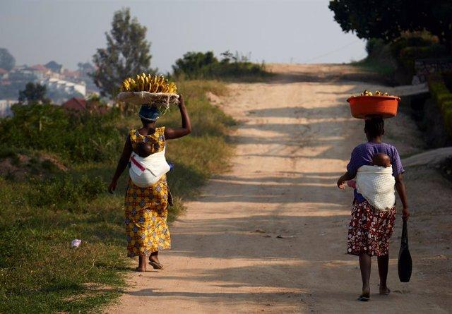 Archivo - 30 August 2019, Rwanda, Kigali: Two women walk down the street selling bananas. Photo: Allison Dinner/ZUMA Wire/dpa