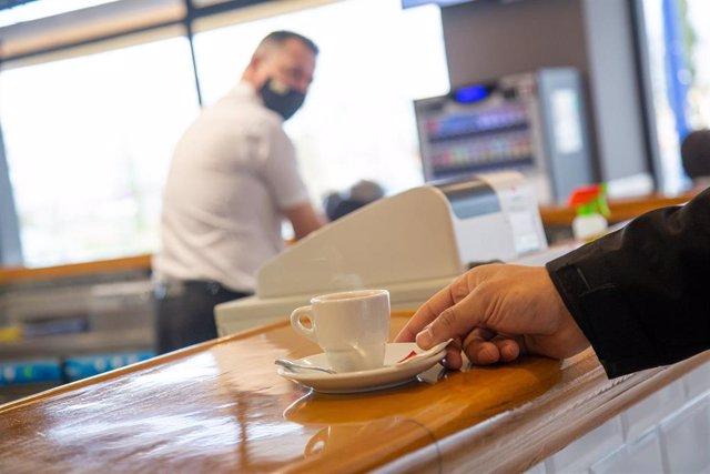 Archivo - Un cliente recoge una taza de café en el pacense Bar Venero, durante el primer día de apertura de bares y restaurantes en Badajoz, Extremadura (España), a 12 de febrero de 2021. La hostelería llevaba cerrada en la comunidad desde el pasado 14 de