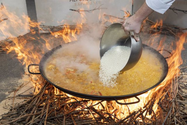 Archivo - Un cocinero echa el arroz en una paella