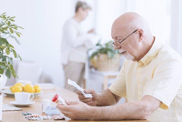 Archivo - Hombre mayor mirando el prospecto de un medicamento.