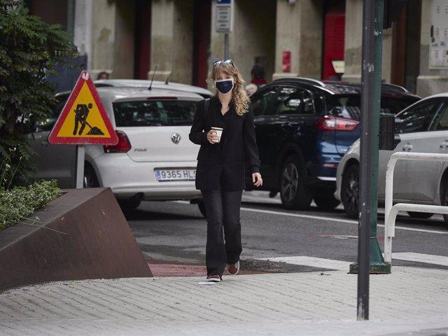 Archivo - Una mujer con mascarilla y un café en la mano en el cuarto día de la Fase 1 en la ciudad de Pamplona
