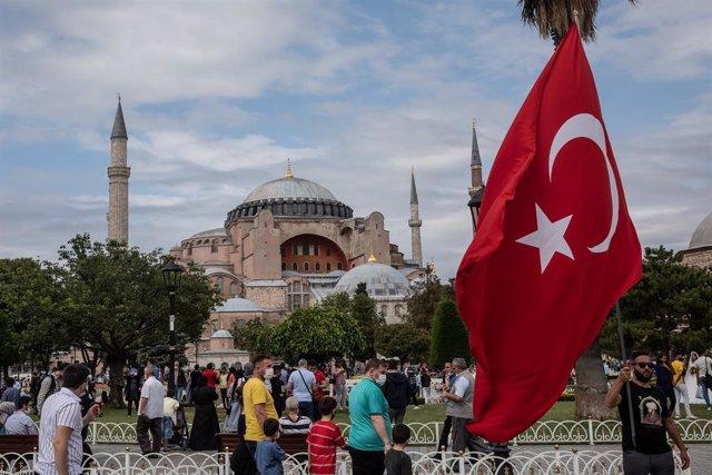 Archivo - Un hombre agita la bandera nacional de Turquía frente a la Mezquita de Santa Sofía en el cuarto aniversario del fallido intento de golpe del 15 de julio de 2016.