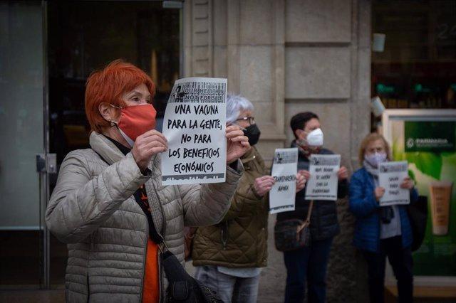 Una mujer sostiene un cartel reclamando un acceso igualitario a las vacunas contra el Covid-19, ante la delegación de la Comisión Europea en Barcelona, situada en el Paseo de Gràcia, este miércoles 7 de abril del 2021.