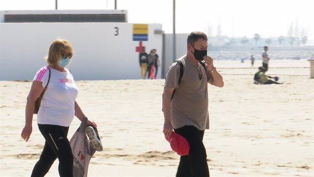 Personas con mascarilla, paseando en una playa.